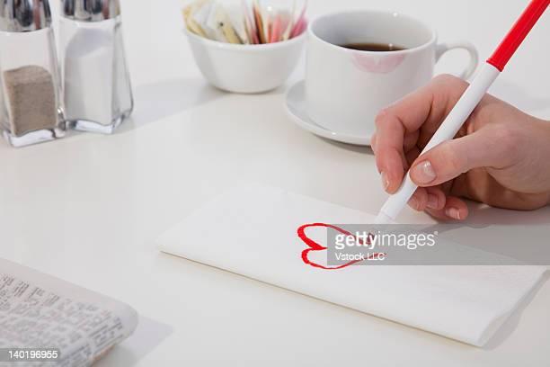 USA, Illinois, Metamora, Close-up of woman's hand drawing heart on napkin