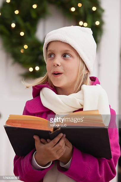 USA, Illinois, Metamora, Girl (6-7) singing Christmas carols