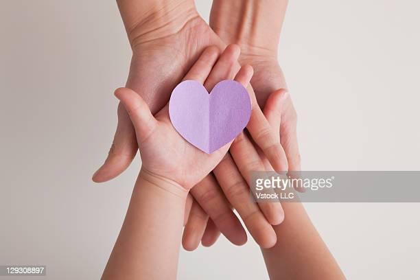 usa, illinois, metamora, hands of mother and daughter (4-5) holding paper heart - muttertag herz stock-fotos und bilder