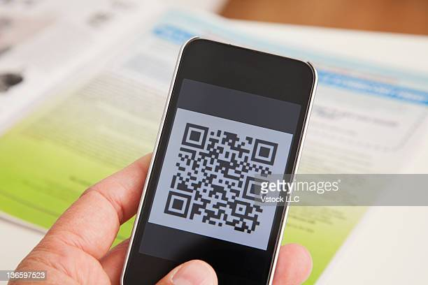 USA, Illinois, Metamora, Male hand holding smart phone displaying code