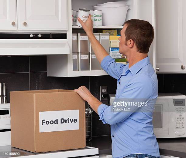 usa, illinois, metamora, man placing canned food in kitchen cupboard - imagenes gratis fotografías e imágenes de stock