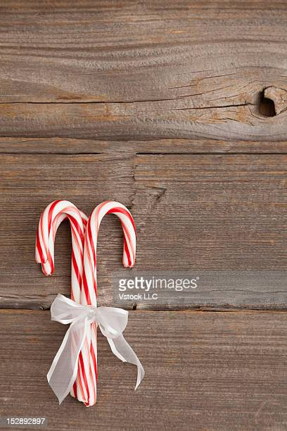 USA, Illinois, Metamora, Peppermint candy canes tied with white ribbon on wooden background