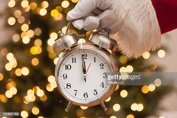 USA, Illinois, Metamora, Santa Claus holding alarm clock