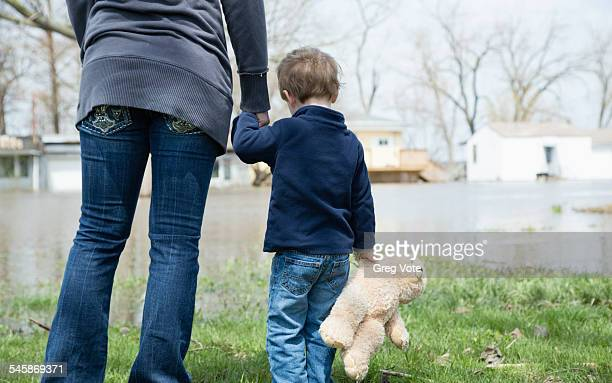 usa, illinois, mother with son standing in flooded town - mother son shower stock photos and pictures