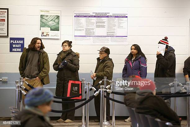 Illinois residents wait in line to apply for or renew their driver's license at a driver services facility on December 10 2013 in Chicago Illinois...