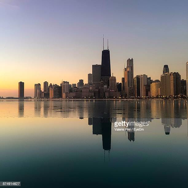 illinois river by cityscape against clear sky - hancock building chicago stock photos and pictures