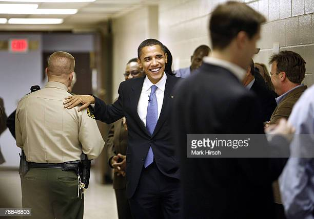 Illinois Senator Barack Obama pats a Blackhawk County Sheriff's deputy on the back as he arrives for a campaign stop at the Central Middle School...