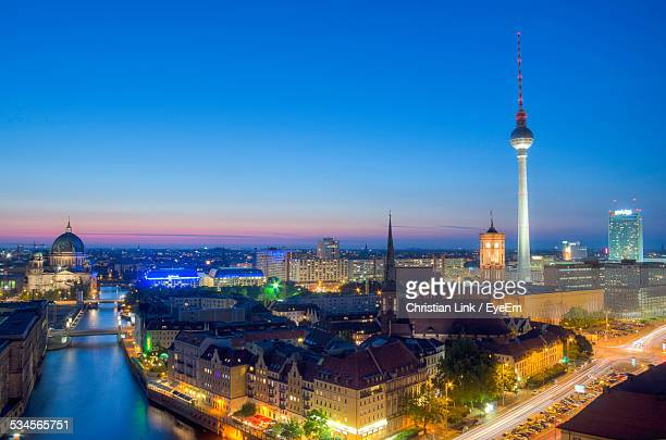 Illuminated Alexanderplatz In City Against Clear Blue Sky