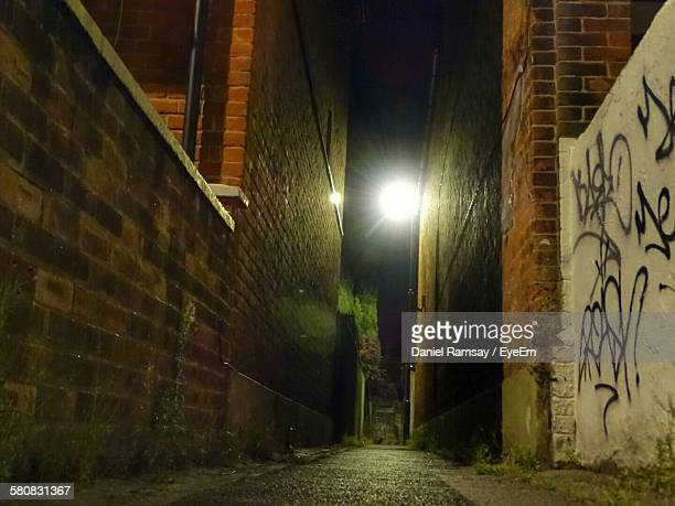 Illuminated Alley Amidst Buildings At Night