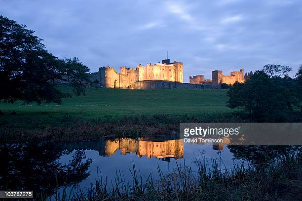 illuminated alnwick castle reflected in still waters of river aln at dusk. - alnwick castle stock pictures, royalty-free photos & images