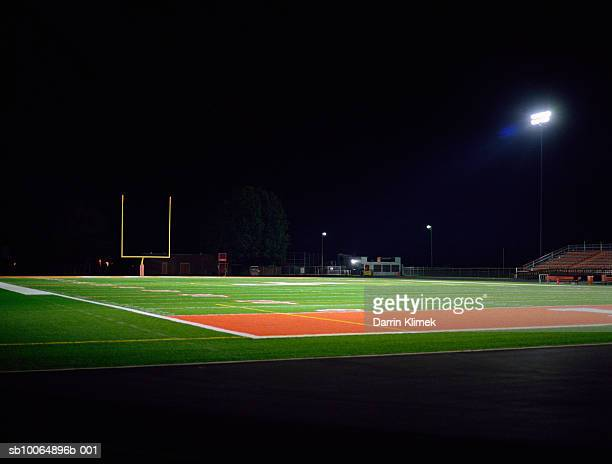 illuminated american football field at night - campo de fútbol americano fotografías e imágenes de stock