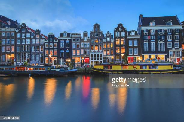 Illuminated Amsterdam canal at dusk, Netherlands