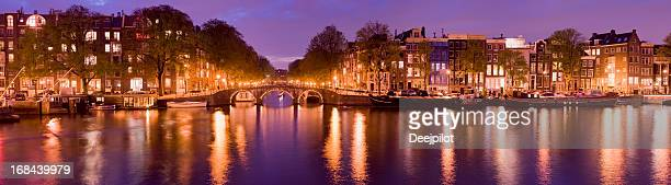 Illuminated Amsterdam Canal at dusk.