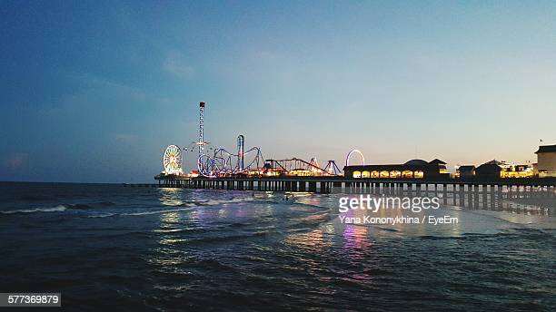 illuminated amusement park on beach against sky at sunset - galveston stock pictures, royalty-free photos & images