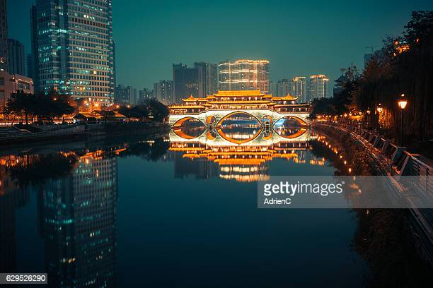 Illuminated Anshun Bridge with reflection in a modern city