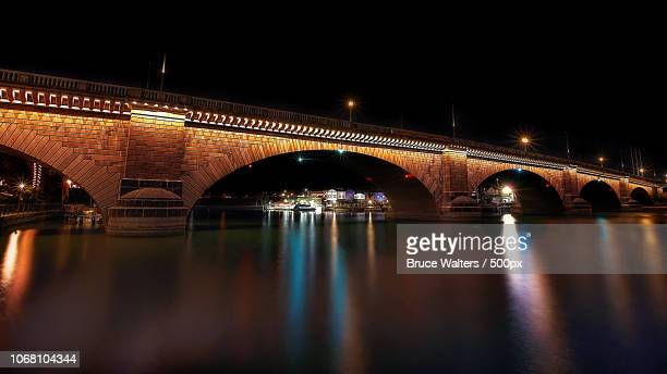 illuminated arch bridge in night - london bridge arizona stock pictures, royalty-free photos & images