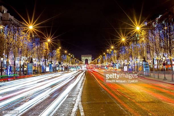 illuminated avenue des champs-elysees and arc de triomphe at night - avenue des champs elysees stock photos and pictures