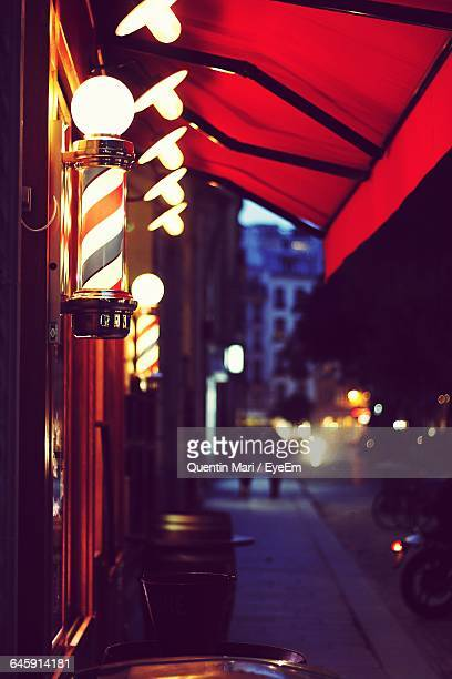 illuminated barbers pole on sidewalk in city at night - barber pole stock photos and pictures