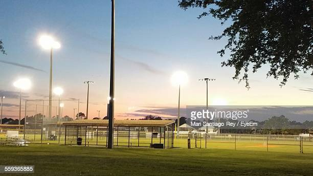 Illuminated Baseball Field Against Sky During Sunset
