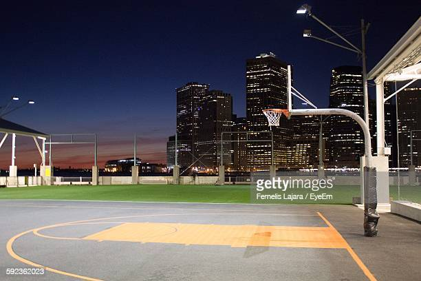 Illuminated Basketball Court Against Sky In City