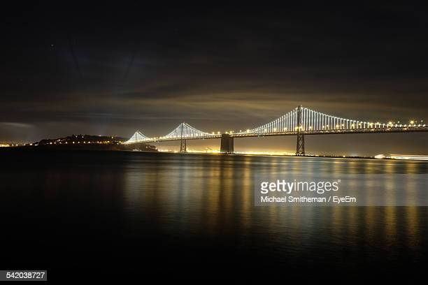 illuminated bay bridge over river at night - bay bridge stock pictures, royalty-free photos & images