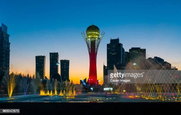 illuminated bayterek tower and fountain in city against clear blue sky - hauptstadt stock-fotos und bilder