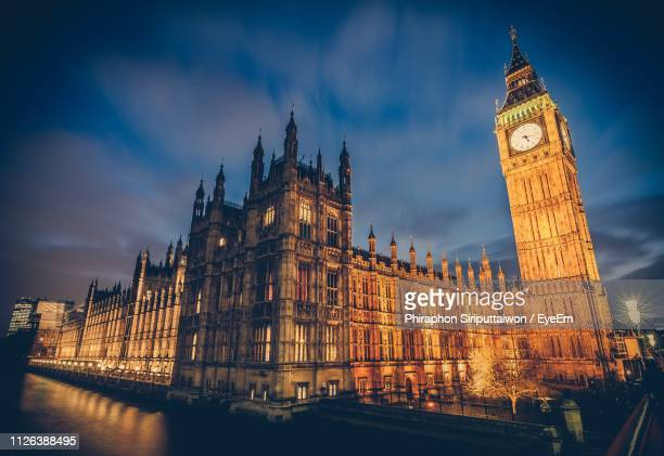 Illuminated Big Ben Tower By Parliament Building In City At Dusk