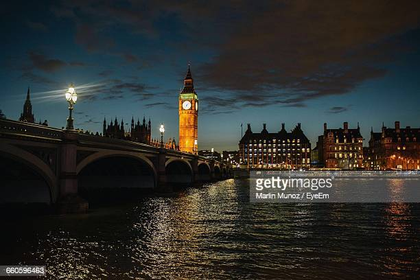 illuminated big ben with westminster bridge over thames river against sky at night - city of westminster london stock pictures, royalty-free photos & images