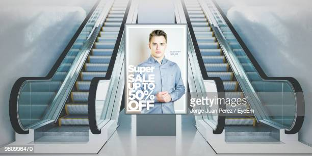 illuminated billboard amidst escalator - advertisement stock pictures, royalty-free photos & images