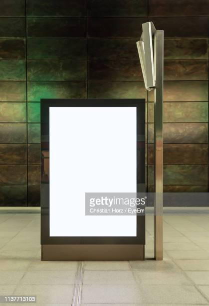 illuminated blank billboard on street at night - vertikal stock-fotos und bilder