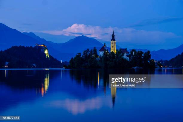 Illuminated Bled Island Blejski otok with the pilgrimage church dedicated to the Assumption of Mary seen across Lake Bled Blejsko jezero at night