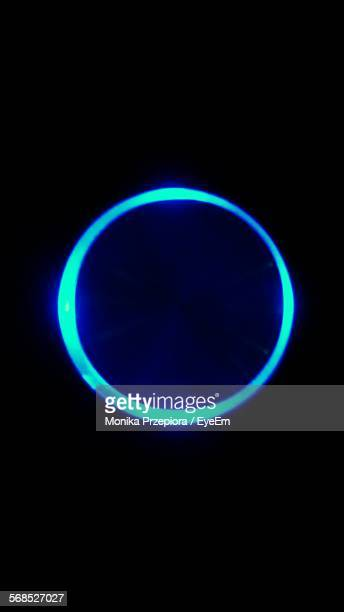 Illuminated Blue Circle Against Black Background