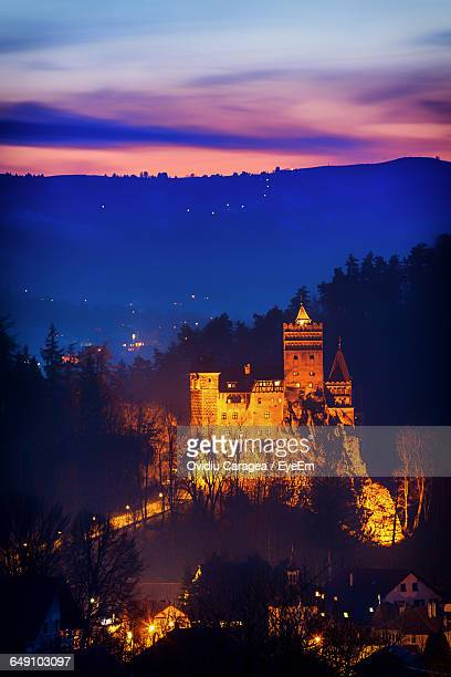 illuminated bran castle by mountain against sky at dusk - transylvania stock pictures, royalty-free photos & images