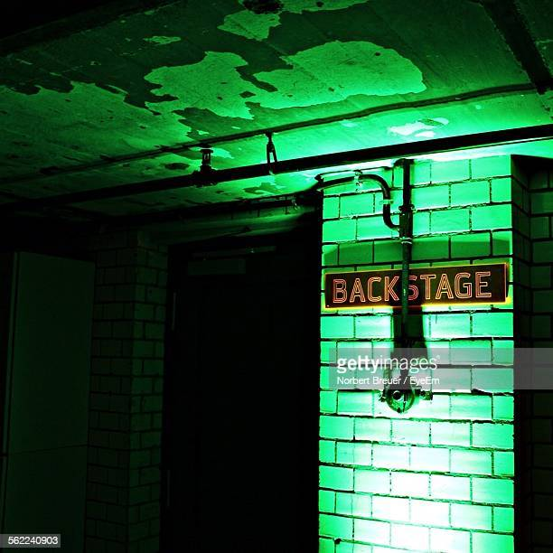 illuminated brick wall with backstage text in dark - backstage stock pictures, royalty-free photos & images