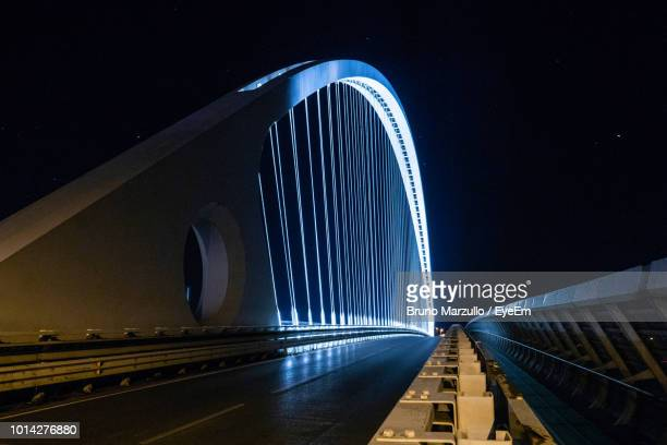 illuminated bridge against sky at night - reggio emilia stock pictures, royalty-free photos & images