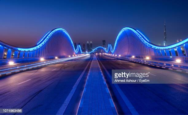 illuminated bridge against sky at night - parallel stock photos and pictures