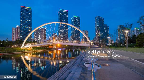 illuminated bridge and buildings against sky at night - songdo ibd stock pictures, royalty-free photos & images