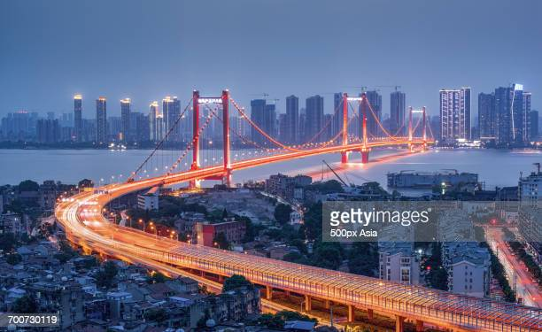 illuminated bridge at dusk - wuhan stock photos and pictures