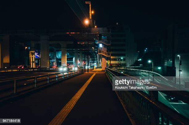illuminated bridge in city against sky at night - midnight stock pictures, royalty-free photos & images