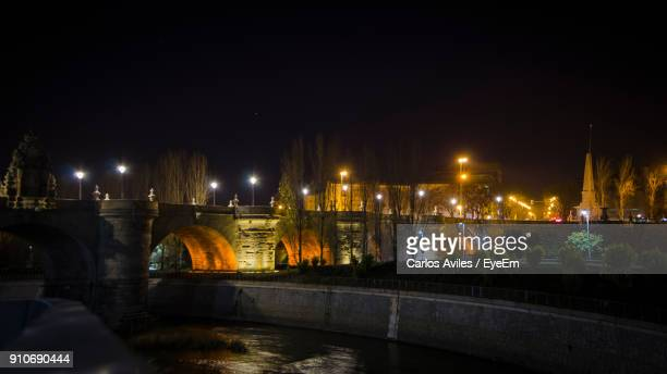 illuminated bridge over canal against sky at night - carlos aviles stock pictures, royalty-free photos & images