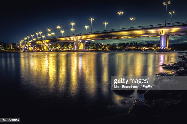illuminated bridge over lake against sky in city at night - jyväskylä stock pictures, royalty-free photos & images