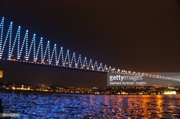 illuminated bridge over river against clear sky at night - gerhard schimpf stock photos and pictures