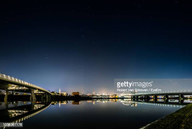 illuminated bridge over river against sky at night - nijmegen stock pictures, royalty-free photos & images