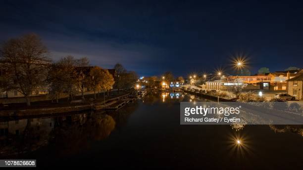illuminated bridge over river against sky at night - chichester stock pictures, royalty-free photos & images