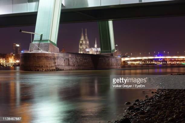 illuminated bridge over river against sky at night - north rhine westphalia stock pictures, royalty-free photos & images