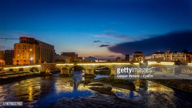 illuminated bridge over river against sky at night - skopje stock pictures, royalty-free photos & images