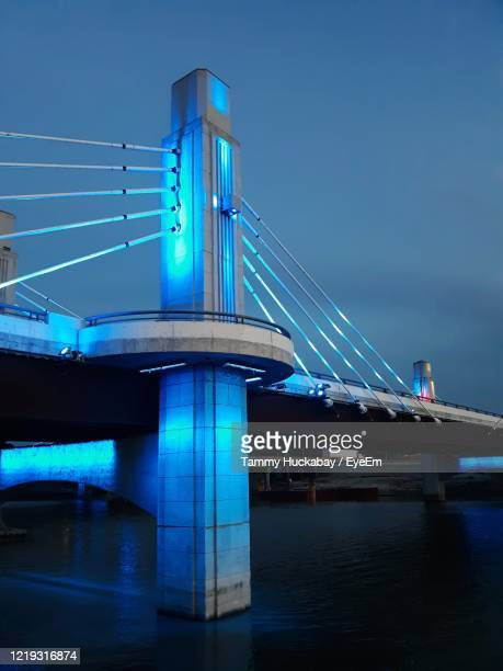 illuminated bridge over river against sky at night - waco foto e immagini stock