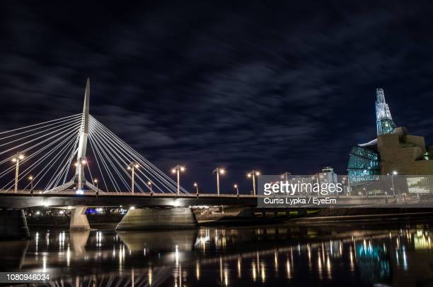 illuminated bridge over river against sky in city at night - winnipeg stock pictures, royalty-free photos & images
