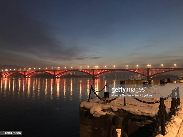 illuminated bridge over river against sky in city at night - krasnoyarsk stock pictures, royalty-free photos & images
