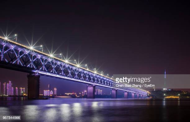 illuminated bridge over river against sky in city at night - wuhan stock photos and pictures